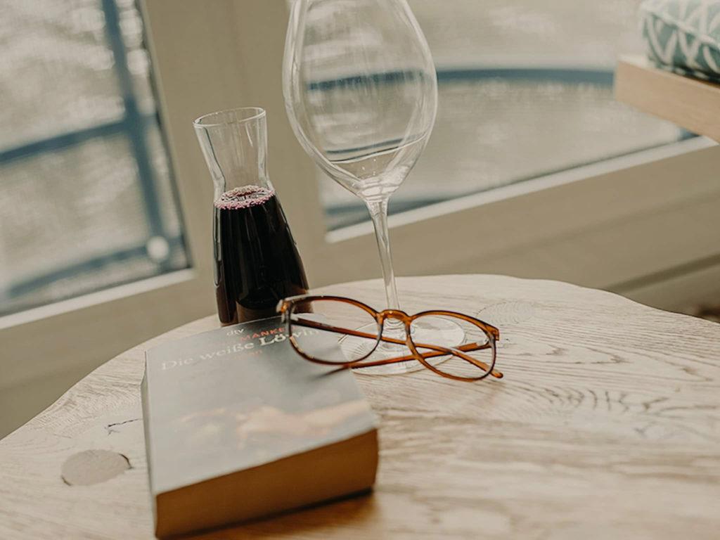 Tisch mit Buch und Wein Schlafzimmer Hotel Sendlhofer's Bad Hofgastein