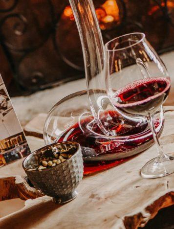 Weinglas und Karaffe vor Kamin Hotel Sendlhofer's Bad Hofgastein